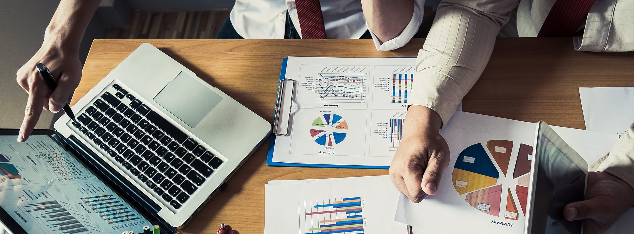 Business person analyzing financial statistics displayed on a desk.