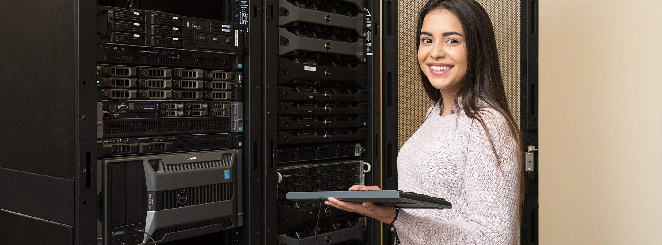 An African American woman standing at a rack of computer servers with a keyboard in her hand.