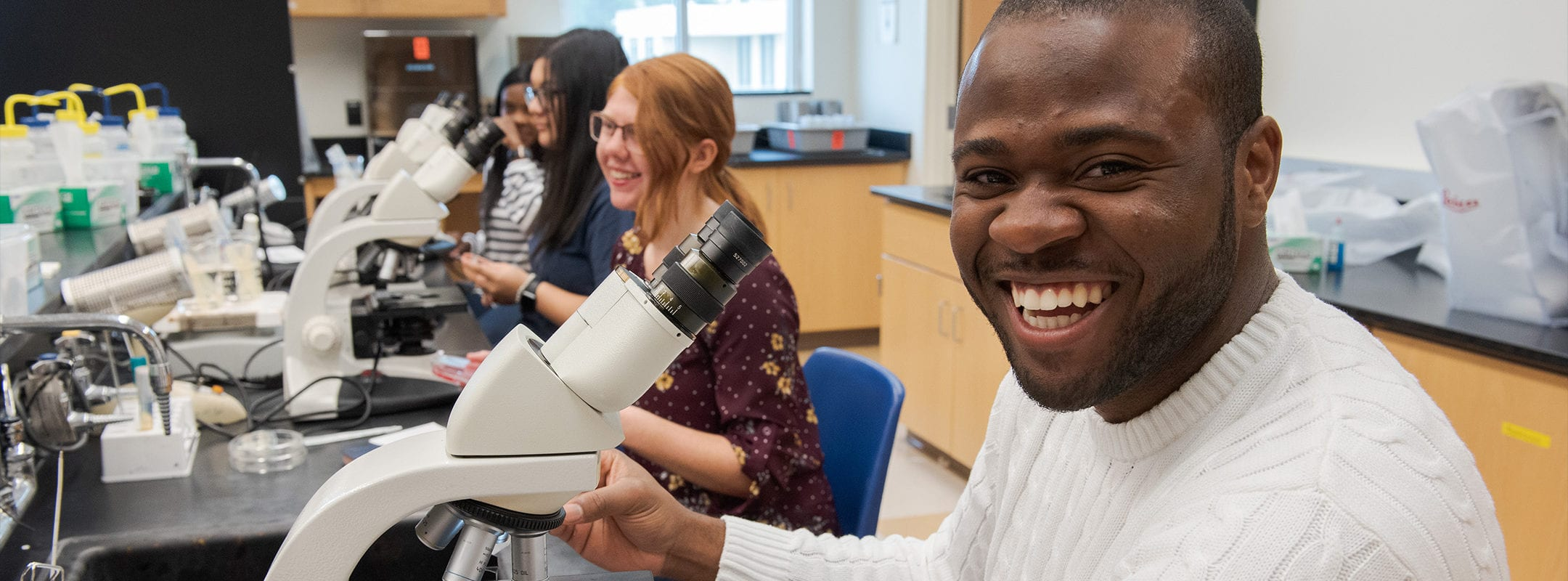 A happy smiling student looking at the camera with a microscope in front of him. Other students are in the class in the background.