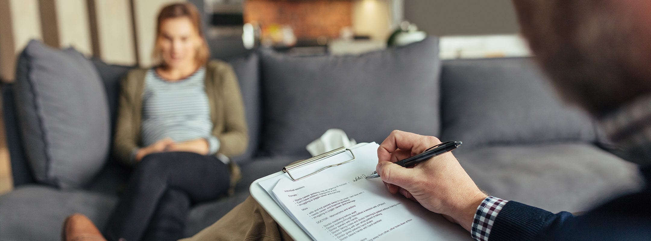 Psychologist taking down notes during therapy session with female patient. Psychotherapist with clipboard and woman patient sitting in background.