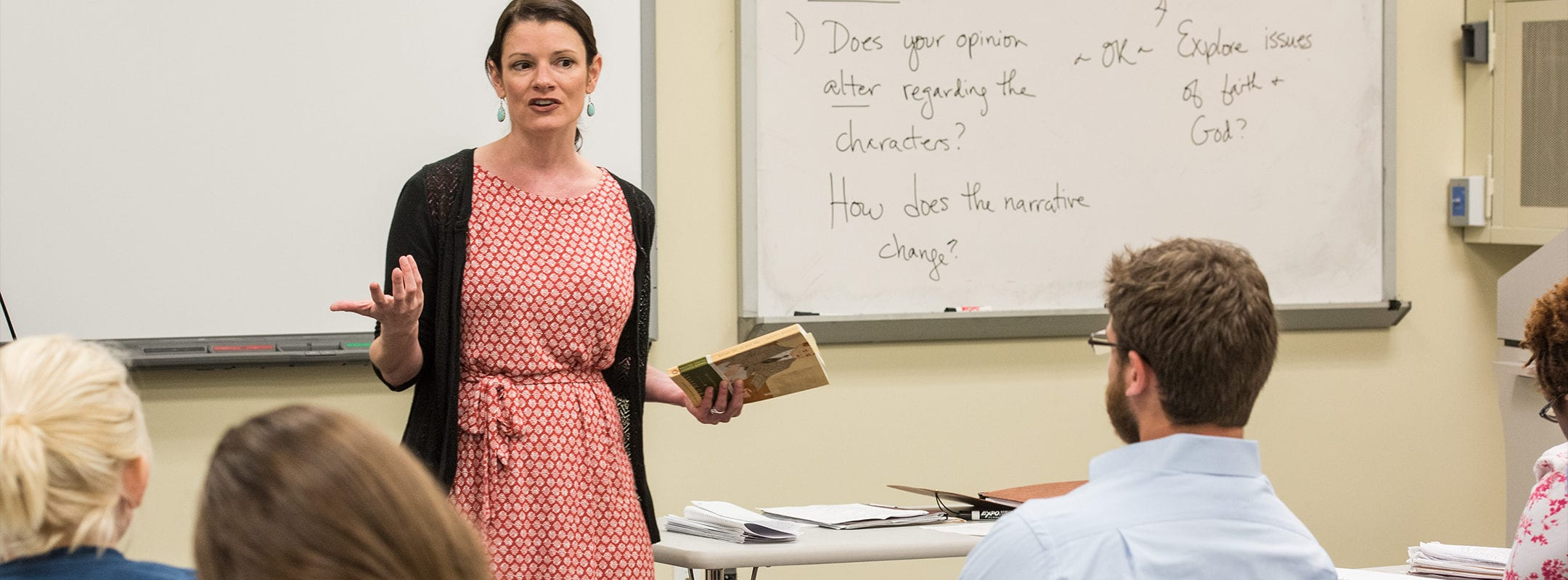 A female professor teaching literature in a classroom.