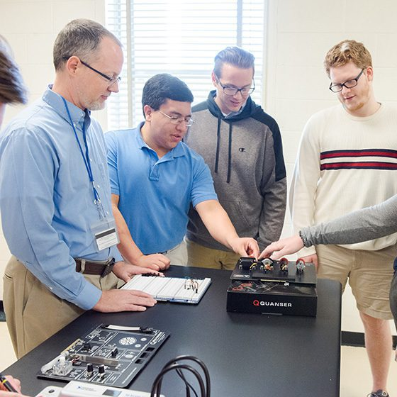 Engineering students and professor looking at electronic equipment.