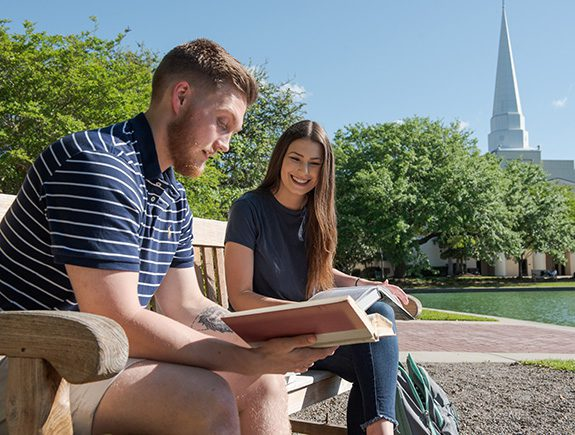 Two students sitting on a bench looking at their text books by the reflection pond at CSU. Lightsey Chapel can be seen in the background.