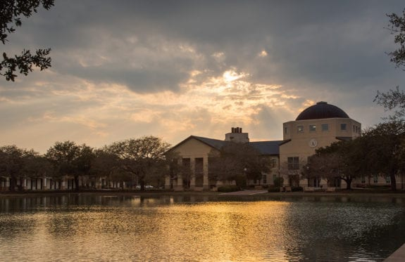 The Science Building with the sun setting behind it casting rays through the clouds. The golden color reflects off of the reflection pond.