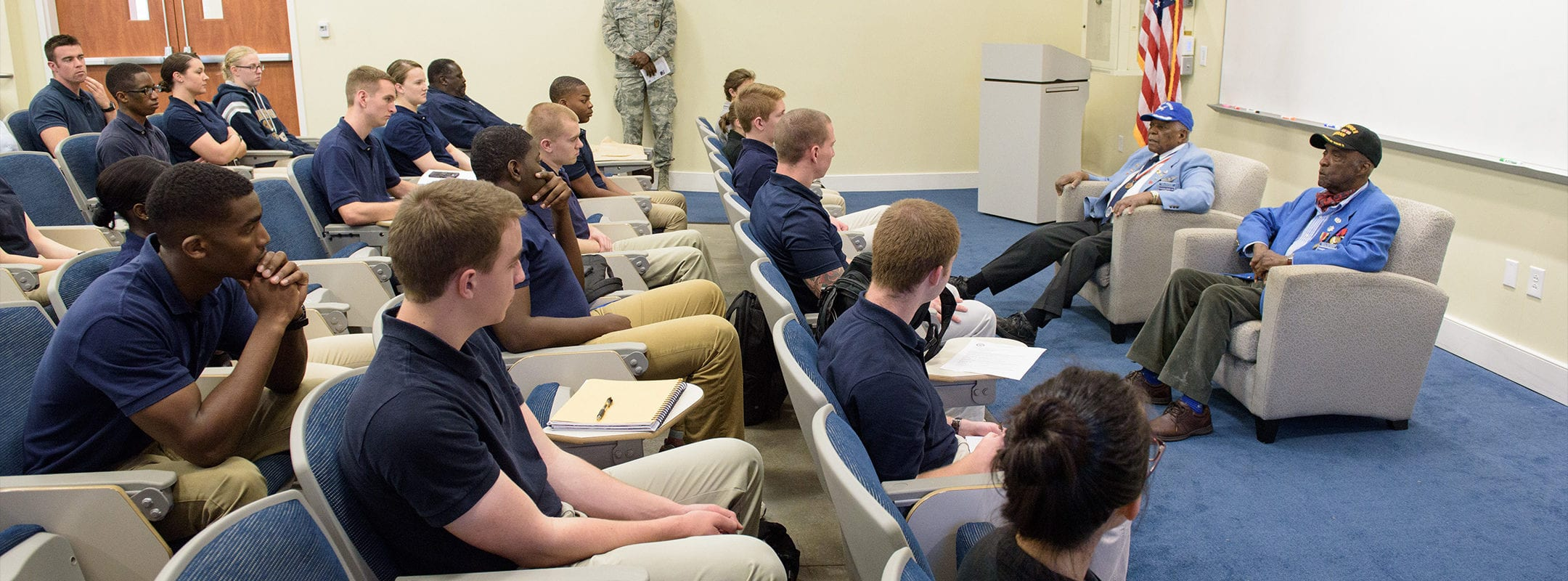 AFROTC students in a classroom listening to two veteran Tuskegee Airmen speak about their experiences in the air force.