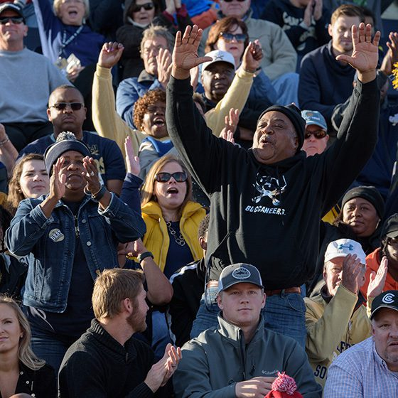CSU alumni cheering in the stands during a football game.