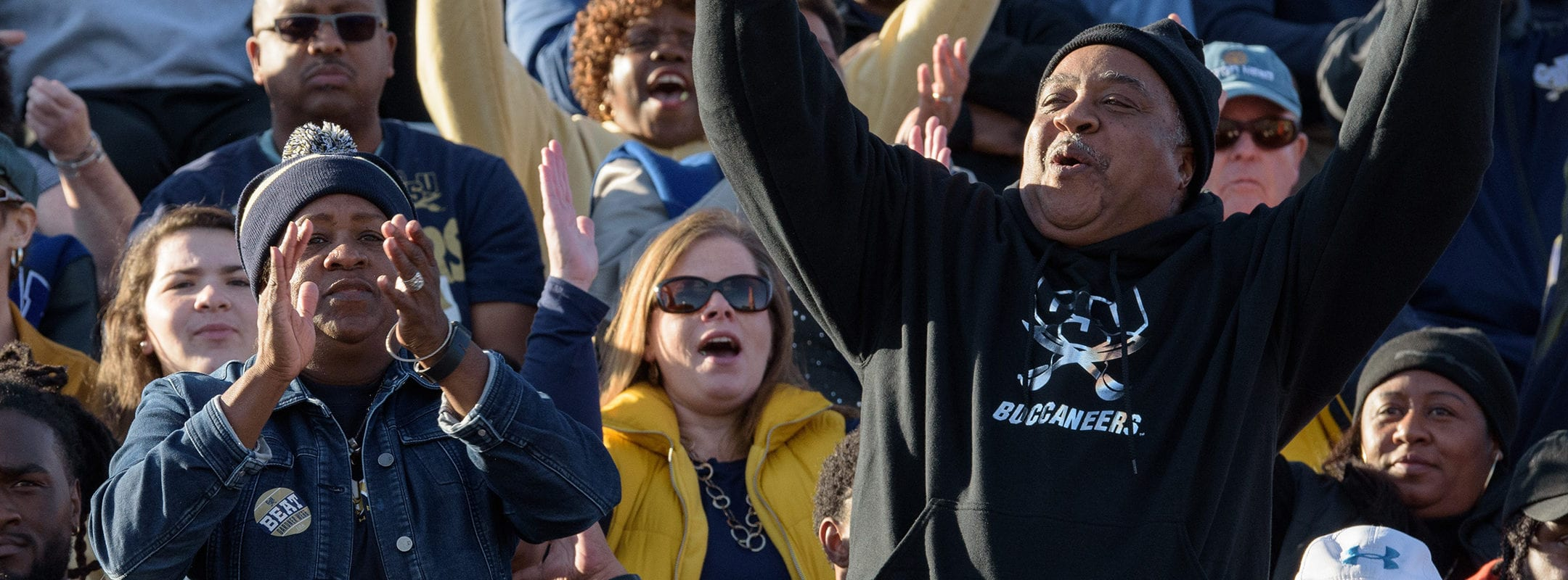 CSU alumni and parents of students cheering in the stands at a football game.