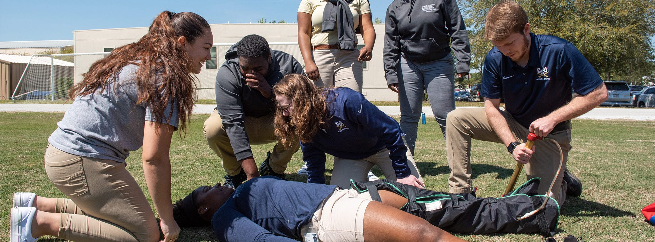 Athletic training students treating a simulated leg injury outside.