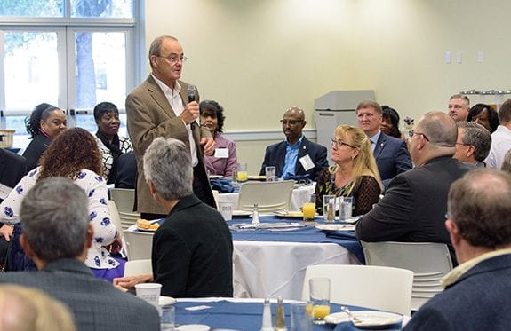 A Board of Visitors member standing up in the middle of the conference room holding a microphone and speaking to guests.