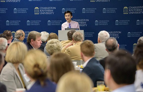 A young asian student standing in front of a backdrop of CSU logos, behind a podium, address a crowd of supporters.