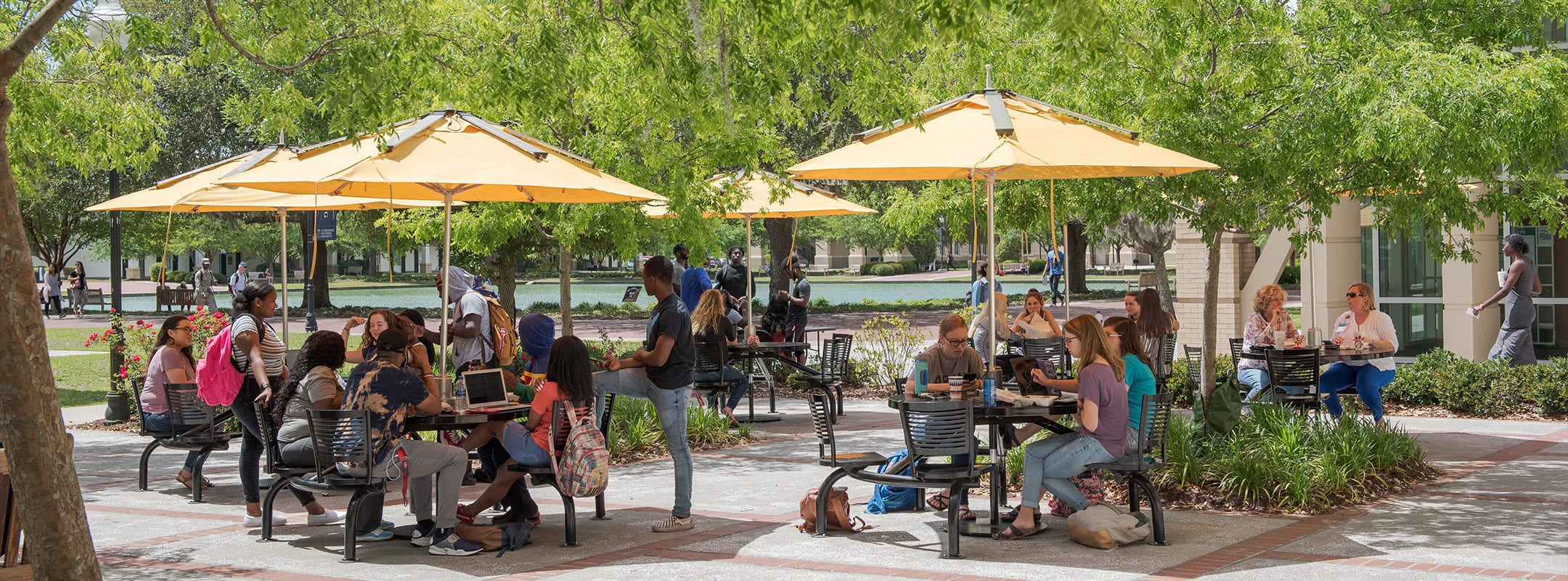Outdoor tables, with umbrellas over them, on CSU's campus, filled with students on lunch break.