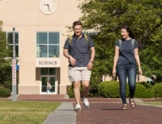 Two students walking down a brick path on CSU's campus with the science building in the background.