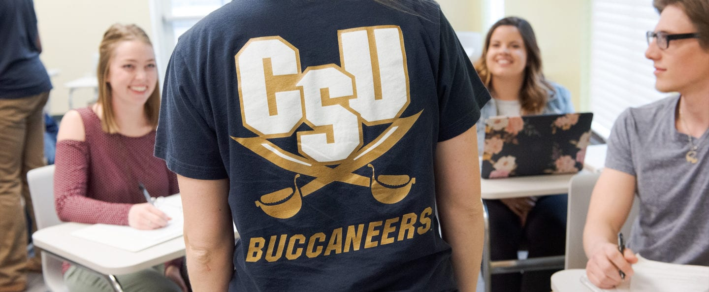 A classroom a students with a view of the back of a students shirt that says CSU Buccaneers.
