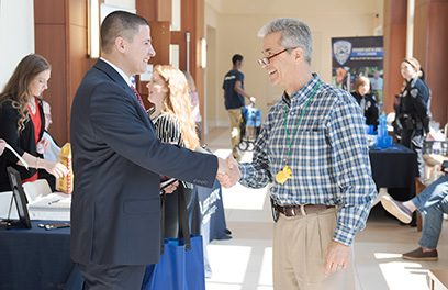 A business dressed student shaking hands with a potential employer at a career fair at CSU.