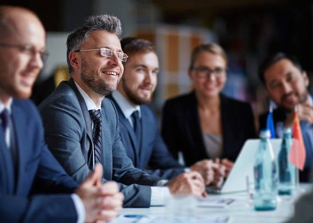 Successful business people sitting at conference table enjoying listening to someone.
