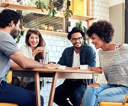 Portrait of cheerful young friends having fun while talking in a cafe.