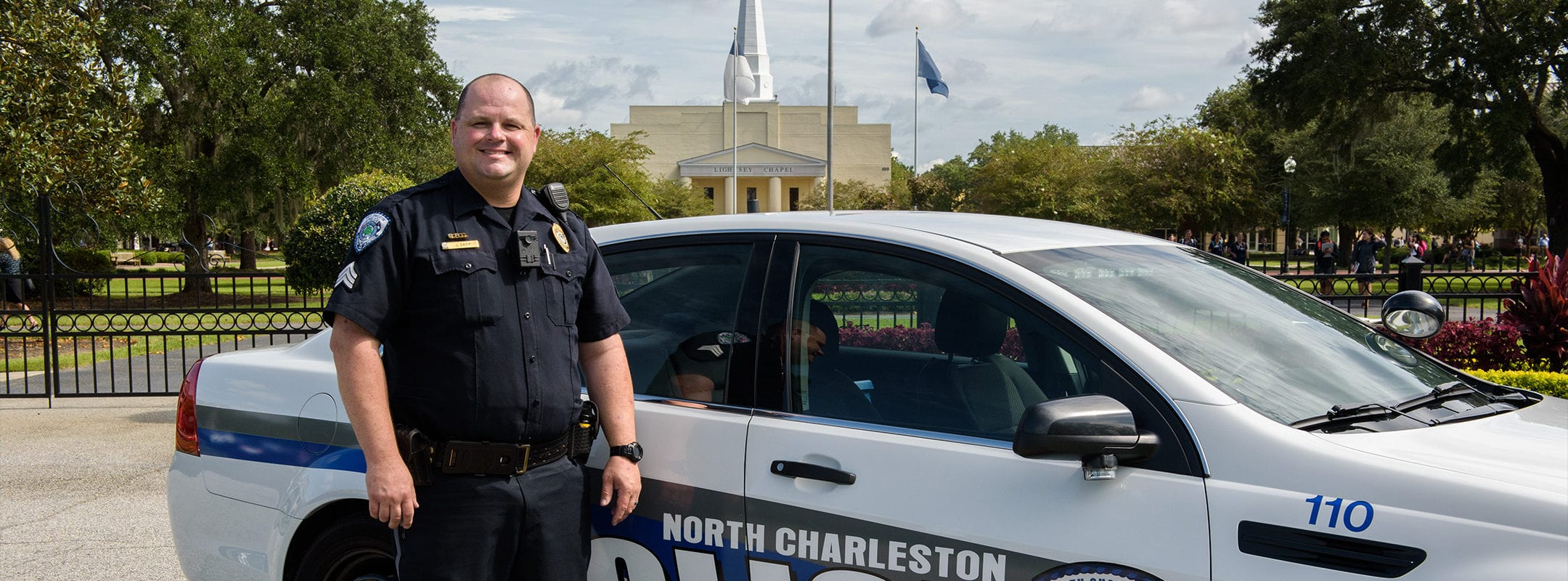A North Charleston police officer standing with his police car in front of Charleston Southern University.
