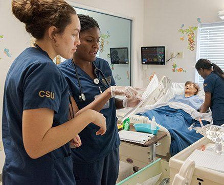 Two nursing students looking at a patients paperwork. In the background is a simulation mannequin.