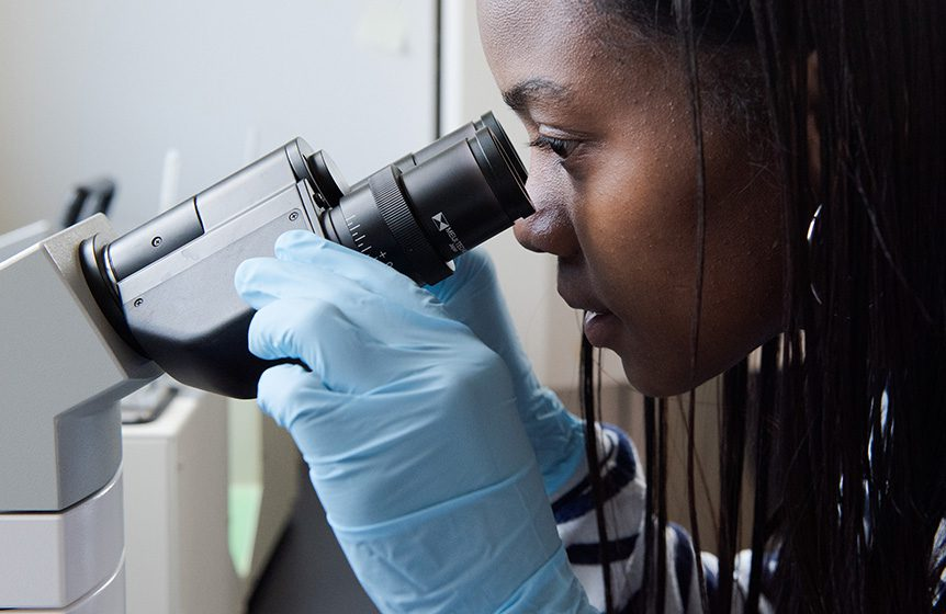 A close up of a young woman wearing blue gloves looking into a microscope.