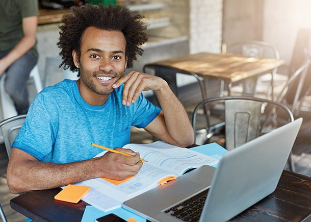 Male student smiling broadly at camera doing his homework while sitting at cafe using laptop.