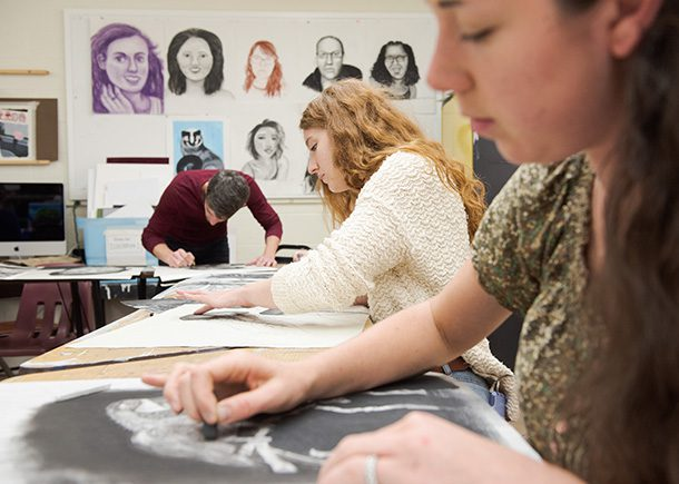 Three students in the CSU art studio drawing with charcoal.