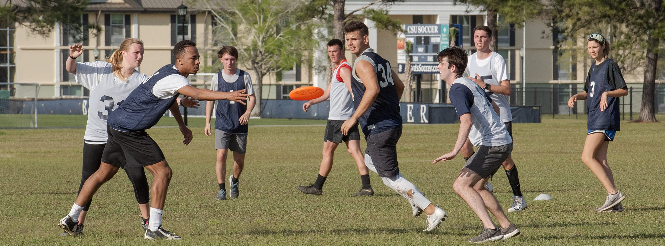 Students on campus playing intramural frisbee football.