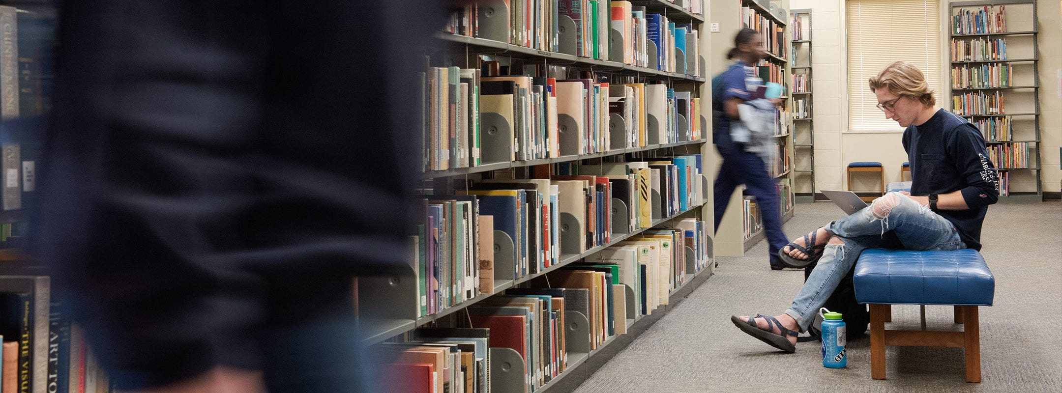 A student studying on a bench in the library while other students walk by.