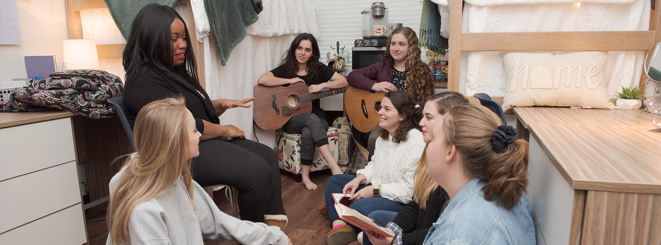Students in their dorm room gathered around talking, two holding guitars.