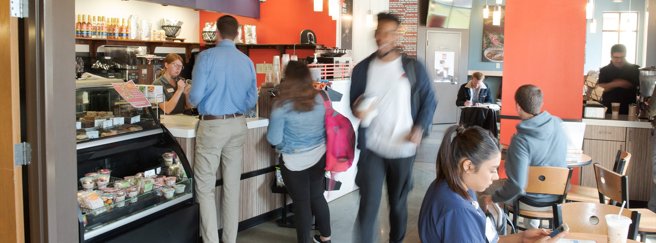 A motion shot of a student walking through the Java City cafe on CSU's campus.