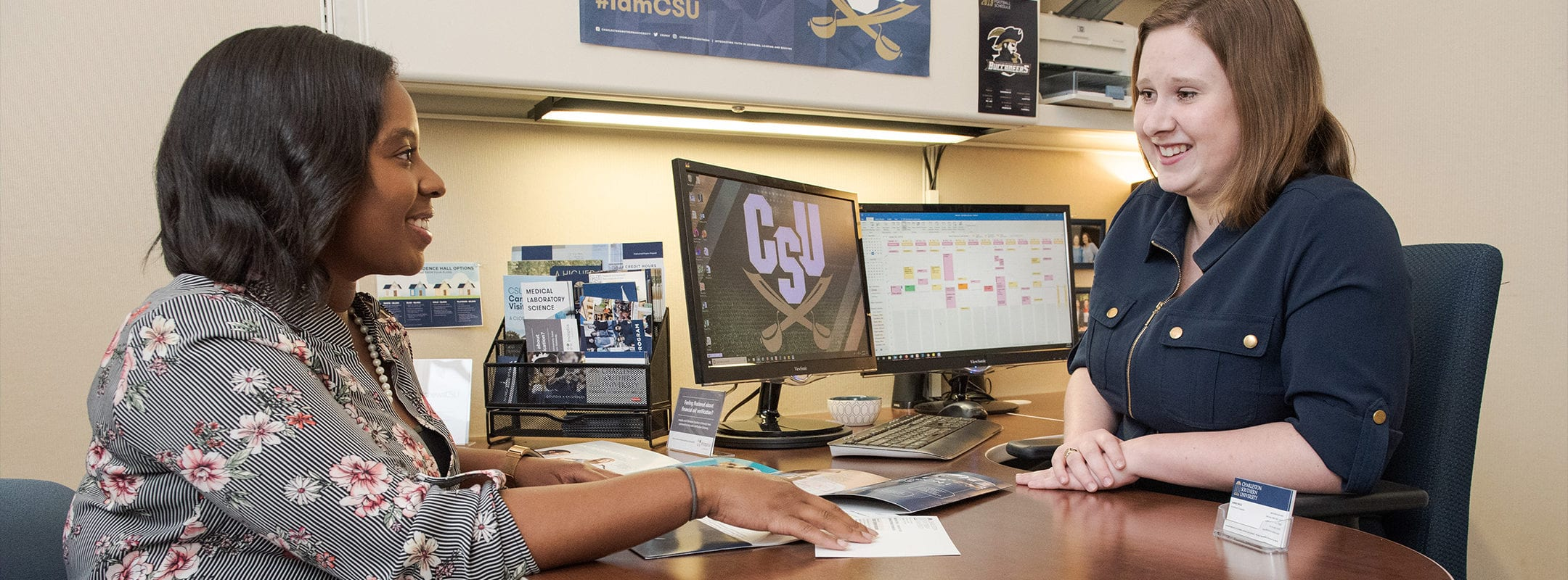 A CSU admissions counselor sitting with a student going over admissions materials.