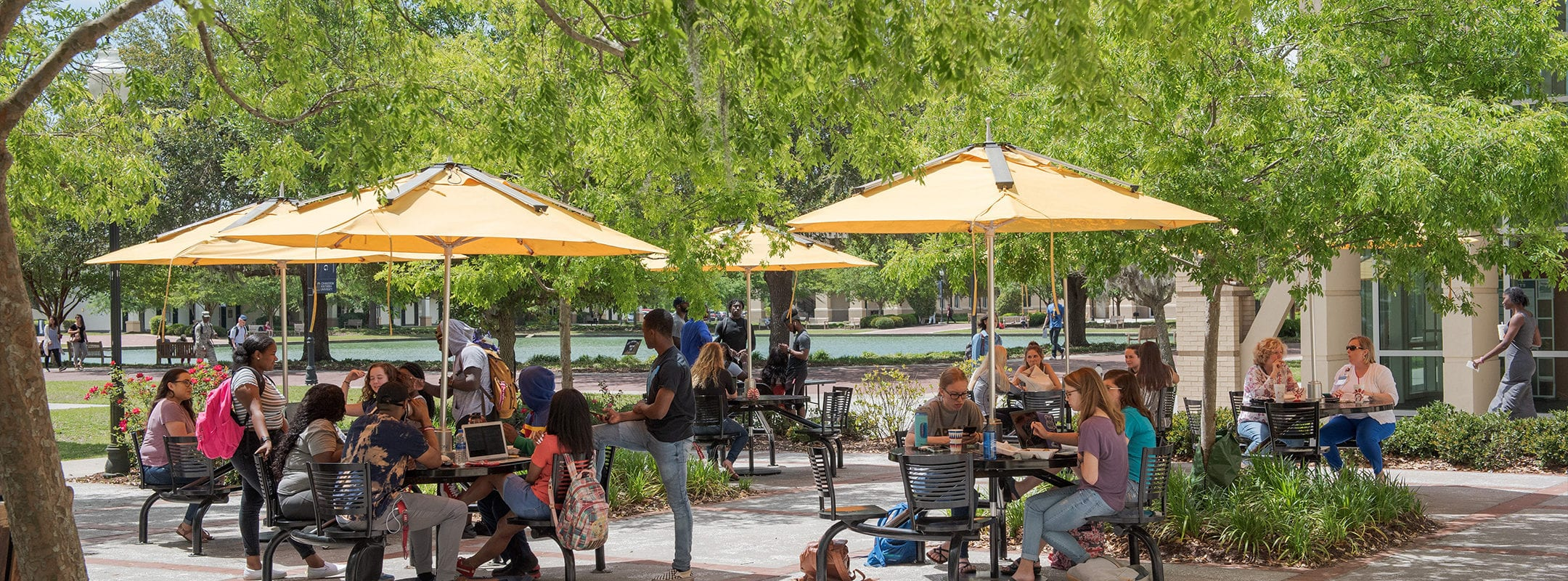 Many students at outside tables next to the CSU dining hall.