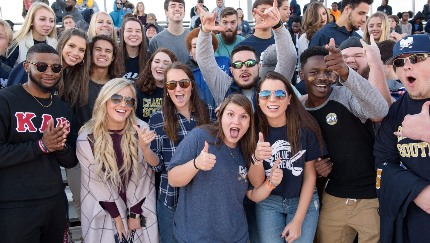 Many students cheering in the stands at a Charleston Southern football game.