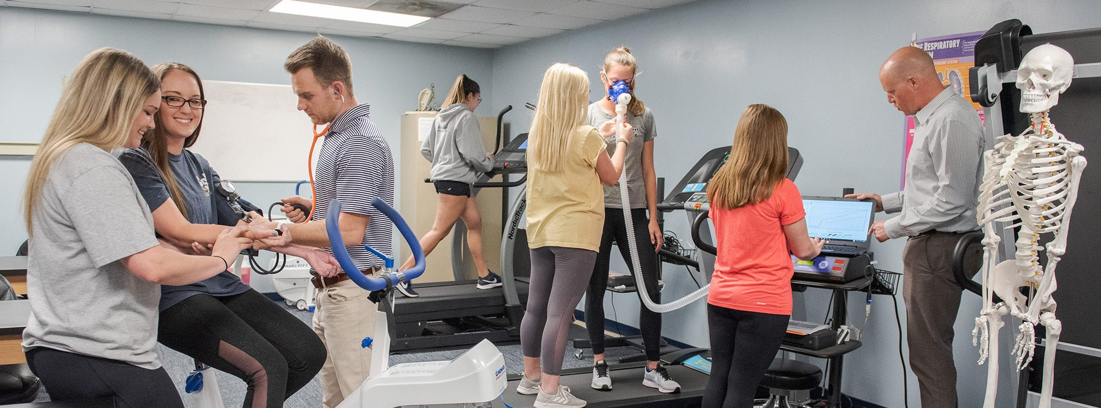Students being tested on various exercise equipment in a classroom gym.