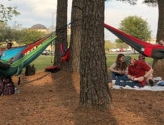 Students hanging in their Eno hammocks in a wooded section of campus.