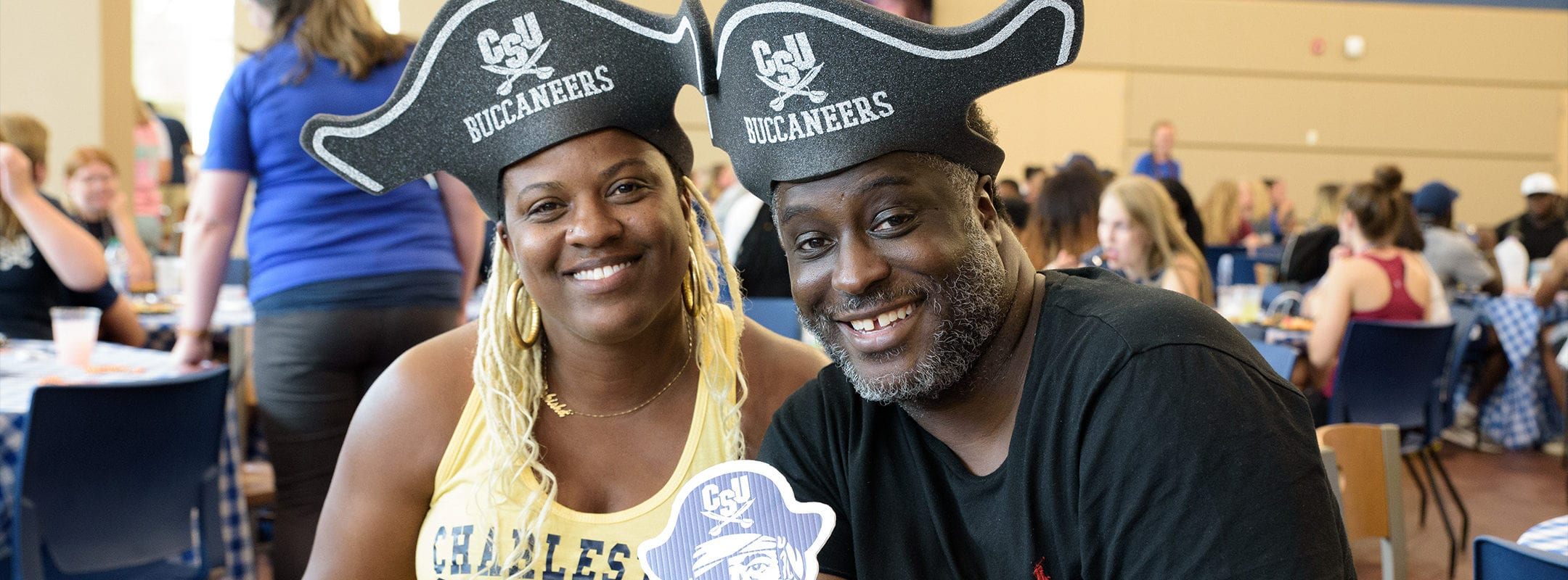 Two CSU parents wearing Buccaneers hats holding a vintage Bucky logo, smiling at the camera in the Dining Hall.