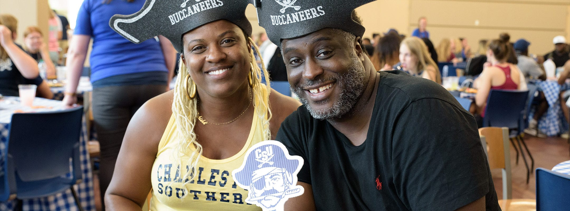 Parents of a CSU student. They are wearing CSU Buccaneers pirate hats.