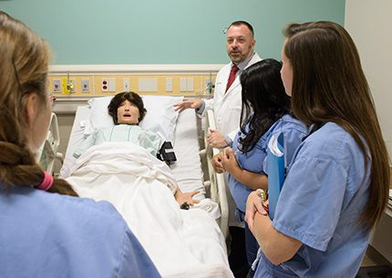 Students and a clinical professor standing around a hospital bed with a simulation patient.