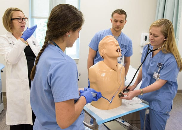 Students in a medical treatment room with a professor working on a dummy patient.
