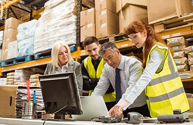 Warehouse managers and worker talking while looking at a computer screen.