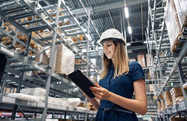 Young woman worker looking for goods with a tablet, checking inventory levels in a warehouse.