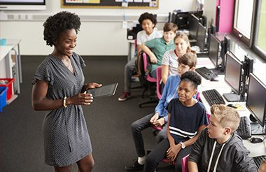 Teacher With Digital Tablet Talking To Line Of High School Students Sitting By Screens In Computer Class