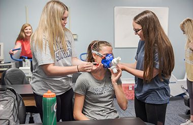 Kinesiology students applying a breathing mask to another student.