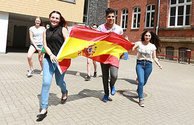 Students running through a courtyard holding the flag of Spain.