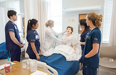 Nurses standing around a simulation mannequin listening to their instructor.