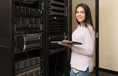 A female student smiling at the camera while standing at a rack of computer servers with a keyboard in her hand.