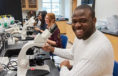 Students smiling in a biology lab classroom as the sit in front of microscopes.