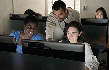 Three students in the CSU Cyber Security room looking at a computer screen together.