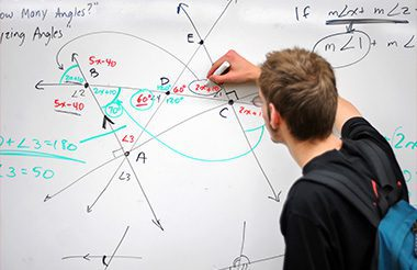 A student writes several complex mathematical formulas, equations, and geometry on a white board.