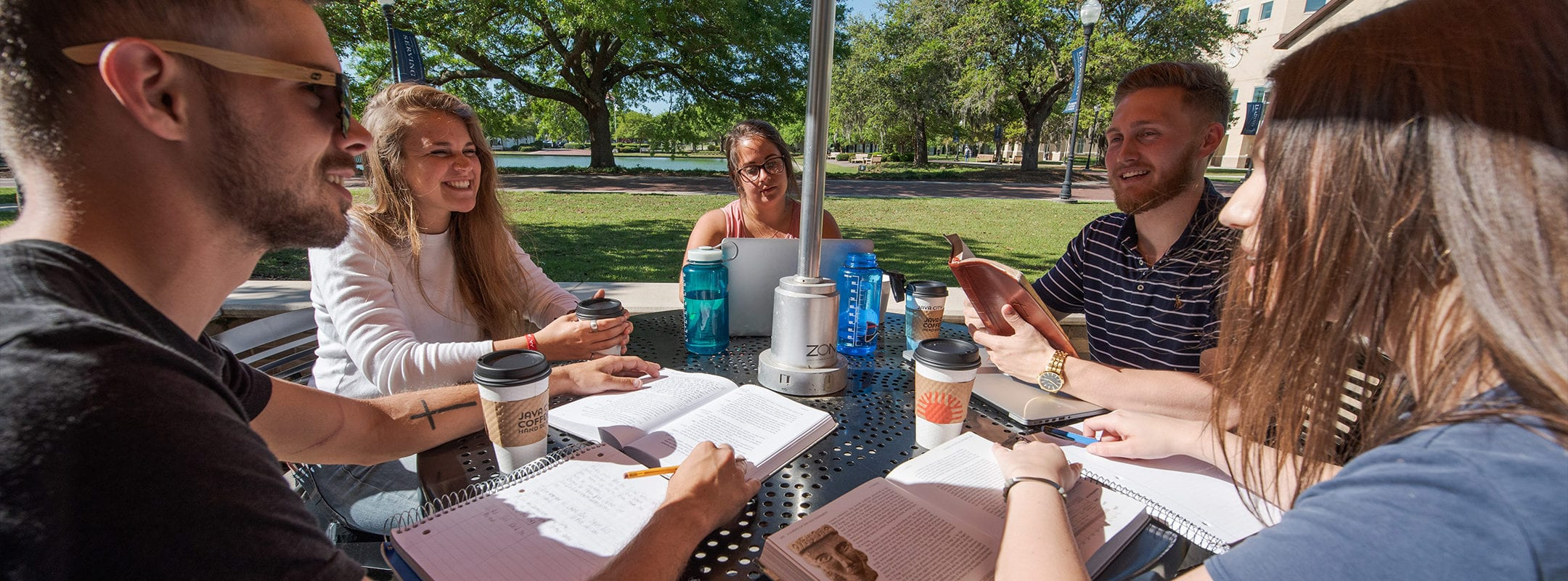 Students studying around a round table outside on the campus of CSU.