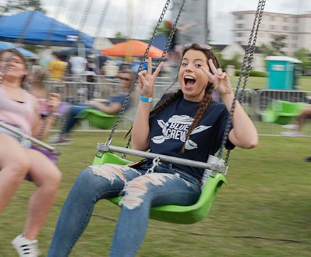 A student smiling while riding the swing ride at the CSU Buc Fever Fair
